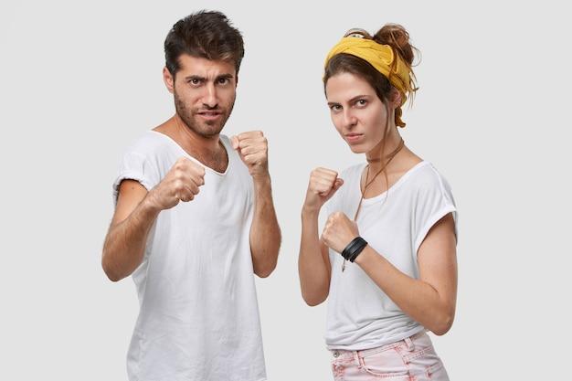Linda senhora severa e seu namorado com a barba por fazer ficam juntos, mantêm as mãos em um gesto defensivo, parecem sérios, prontos para lutar e se proteger, posar contra uma parede branca