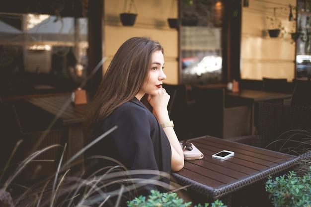 Linda senhora solitária em uma mesa de café parece pensativa