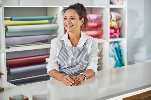 Linda senhora sorrindo enquanto posava perto de rolos de papel de embrulho
