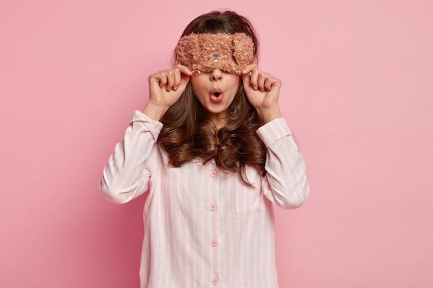 Linda senhora surpreendida cobre os olhos com uma máscara de dormir, usa pijama casual, abre a boca, tem cabelo encaracolado, isolado sobre a parede rosa, se prepara para dormir, posa no quarto. conceito de dormir.