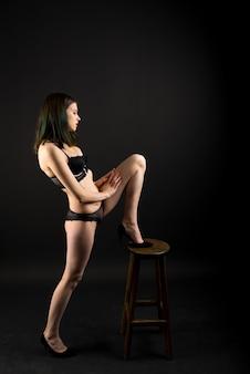 Linda senhora tímida em calcinha de sutiã boudoir de biquíni de renda. forma fina e macia isolada em preto