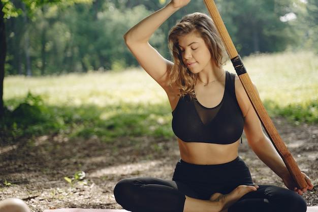 Linda senhora treinando em um parque de verão. morena fazendo ioga. garota em um traje esportivo.