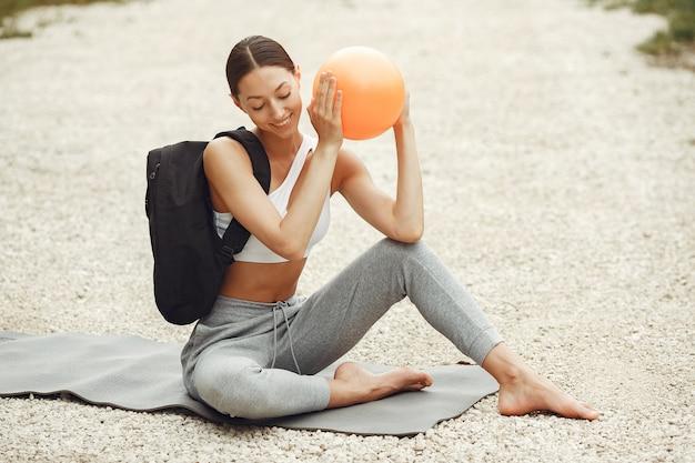 Linda senhora treinando em uma praia de verão. morena fazendo ioga. garota em um traje esportivo.