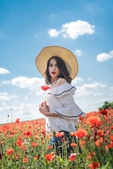 Linda senhora ucraniana sozinha com chapéu de palha no campo de papoulas de flores, dia sexy e ensolarado Foto Premium