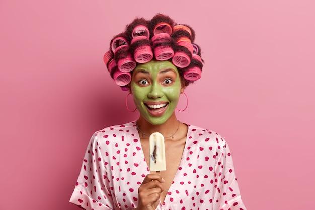 Linda senhora usando máscara para cuidados do rosto usando rolos de cabelo isolados
