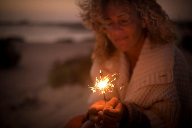 Linda senhora usar e olhar uma luz de fogo brilhante em uma noite de verão. praia e oceano desfocados