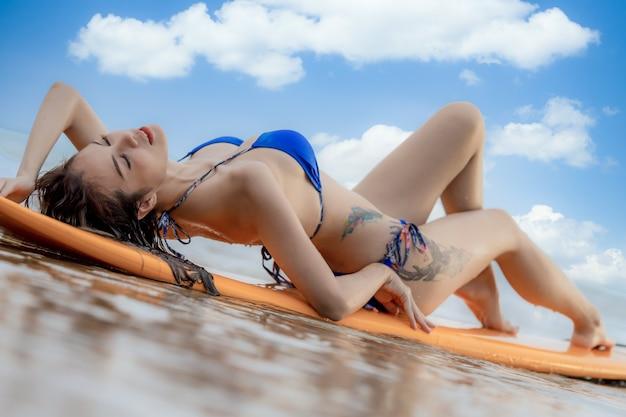 Linda sexy surfista asiática deitada na prancha de surf na praia, surfando garota em biquíni estilo de vida saudável e férias de verão, jovem mulher na praia, esportes aquáticos, surf, férias de verão.