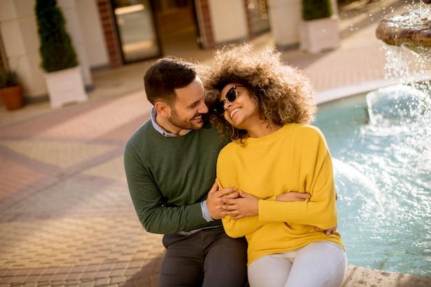 Linda sorridente amor casal sentado perto da fonte em um dia ensolarado