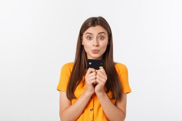 Linda sorridente confiante garota mostrando cartão preto na mão, isolado sobre o branco.