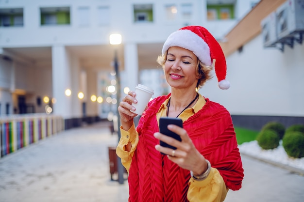 Linda sorridente loira elegante caucasiana sênior mulher com lenço e chapéu de papai noel na cabeça usando telefone inteligente e bebendo café para ir em pé ao ar livre.