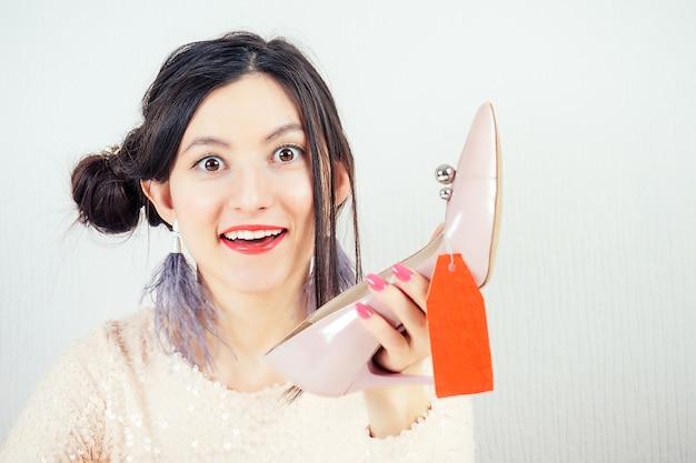 Linda sorridente louca morena louca mulher shopaholic em um vestido rosa, segurando um sapato elegante com uma etiqueta vermelha (etiqueta, guia, tally) na mão. conceito de vendas sazonais e vício em compras