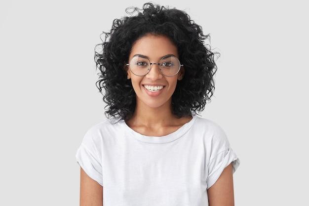Linda sorridente mulher afro-americana com cabelo crespo, sorriso largo, mostra os dentes brancos, usa camiseta casual e óculos, fica de pé na parede e se alegra com o dia de folga. mulher jornalista indoor