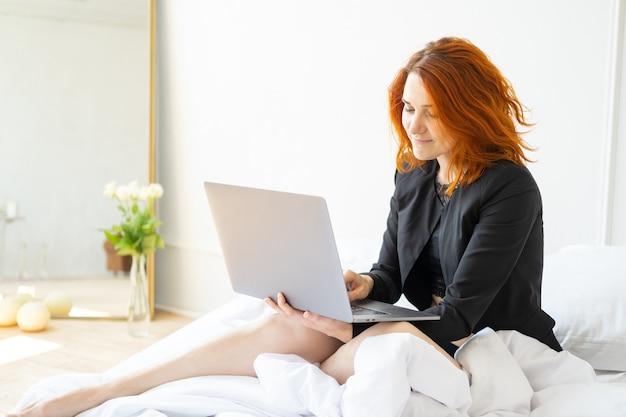 Linda sorridente mulher gengibre de meia-idade, sentada na cama usando o laptop na sala de luz.
