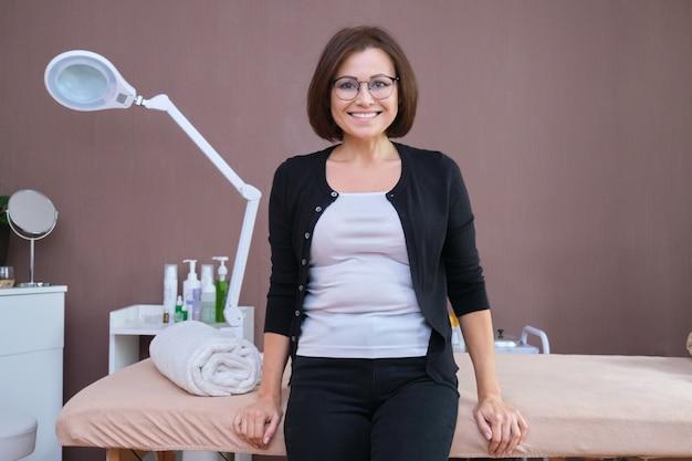 Linda sorridente mulher madura cliente de salão de beleza, posando olhando para a câmera, mesa de massagem de fundo e equipamentos