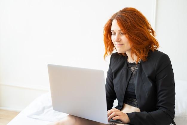 Linda sorridente mulher ruiva de meia-idade sentada na cama usando um laptop em uma sala iluminada