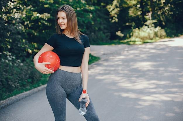 Linda sportsgirl em um parque ensolarado de verão