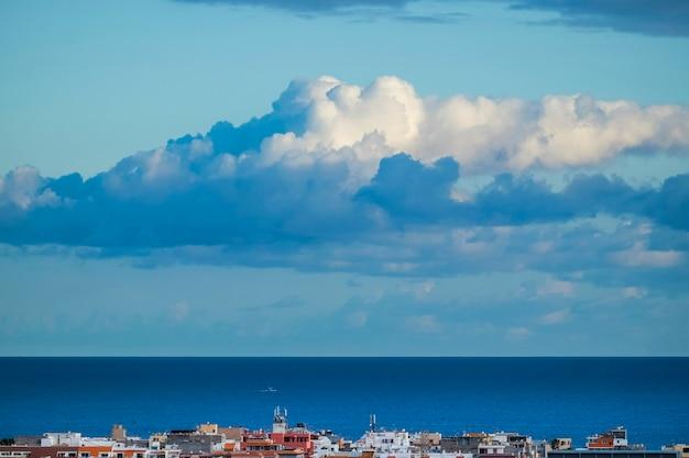 Linda superfície azul da água do mar e linha do horizonte com nuvens brancas no céu e casas coloridas na costa da cidade