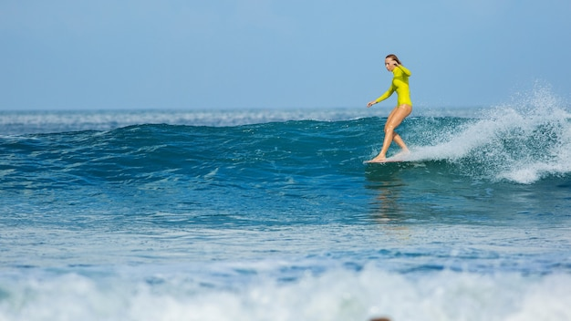 Linda surfista monta um longboard e faz um truque de passeio de nariz.