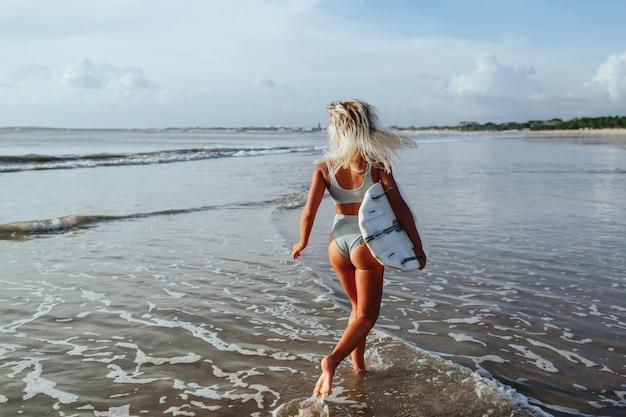 Linda surfista sexy na praia ao pôr do sol