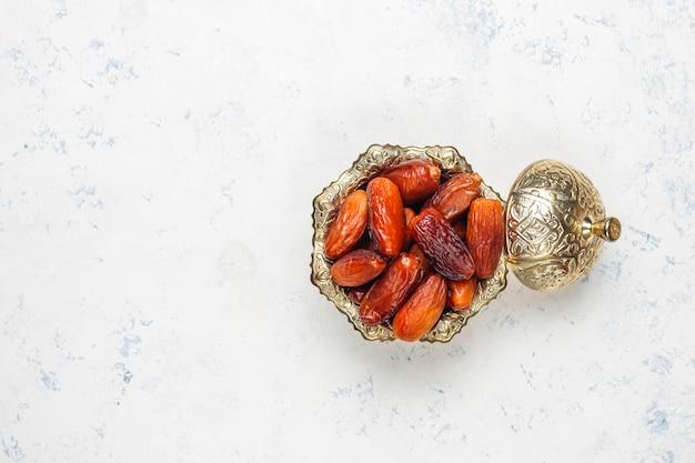Linda tigela cheia de frutas data simbolizando o ramadã, vista superior
