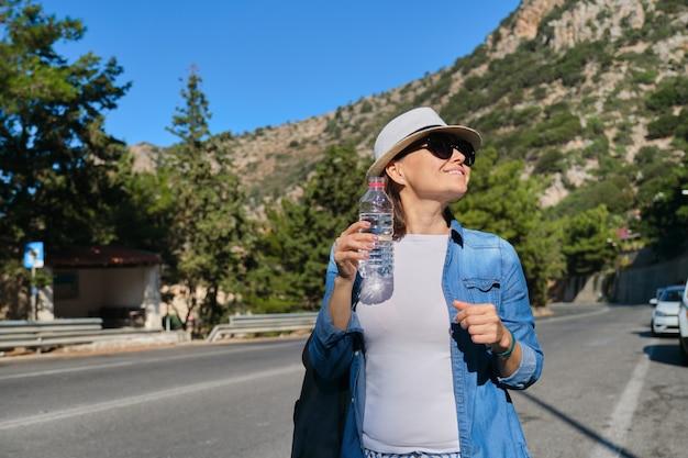 Linda turista feminina adulta removendo a sede, bebendo água de uma garrafa de plástico, viajando na estrada da montanha em um dia ensolarado e quente, copie o espaço