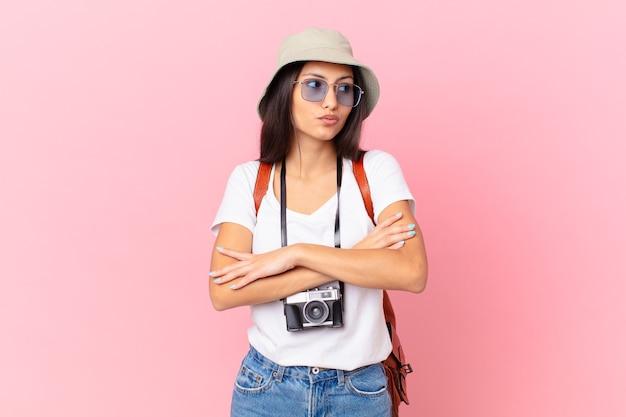 Linda turista hispânica encolhendo os ombros, sentindo-se confusa e insegura com uma câmera fotográfica e um chapéu