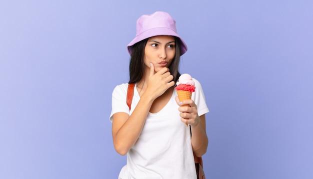 Linda turista hispânica pensando, sentindo-se duvidosa e confusa e segurando um sorvete