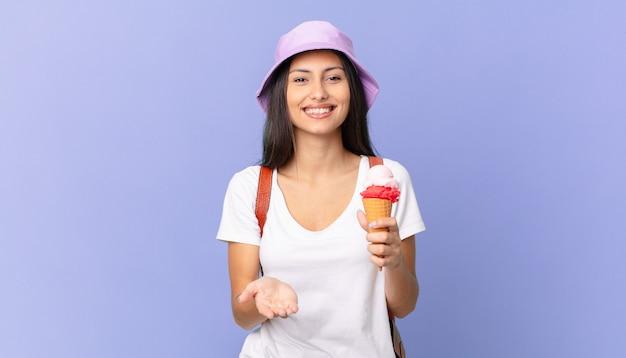 Linda turista hispânica sorrindo feliz com simpática e oferecendo e mostrando um conceito e segurando um sorvete