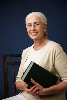 Linda velha alegre segurando o livro.