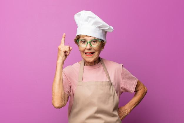 Linda velha mulher madura se sentindo um gênio feliz e animado depois de perceber uma ideia, levantando o dedo alegremente, eureka!