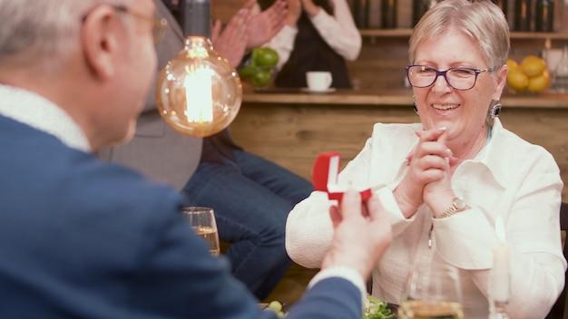 Linda velha senhora cheia de emoções quando o marido está lhe dando um anel. casal romantico. casal de idosos. casal namoro.