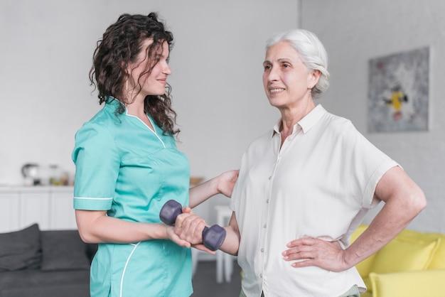 Linda velha senhora está fazendo exercício com halteres com a ajuda de fisioterapeuta