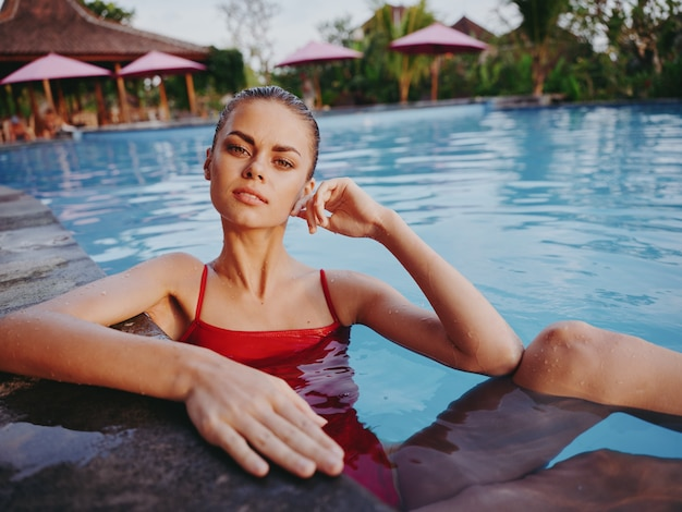 Linda viajante nadando na piscina em um maiô vermelho e tocando seu rosto com a mão
