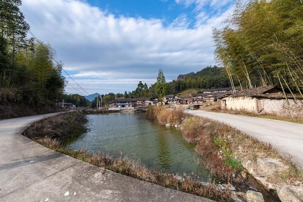 Linda vila de montanha, com lago, céu azul, casa e pastagem