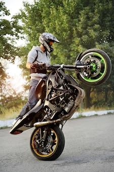 Linda vista lateral de um motociclista andando de motocicleta de maneira extrema