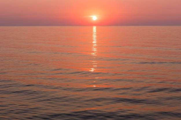 Linda vista para o mar de manhã fascinante com trilha do nascer do sol e do sol na superfície.