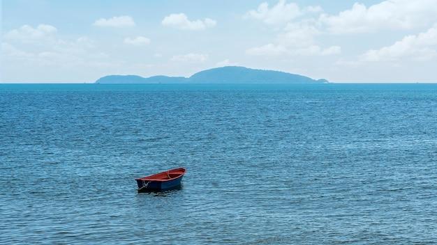 Linda vista para o mar e um pequeno barco flutuando no meio do mar