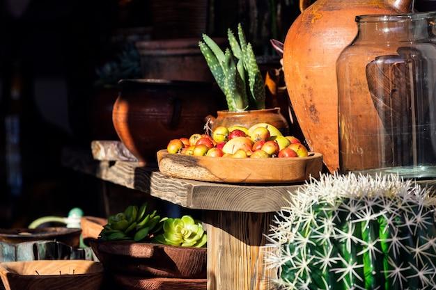Linda vitrine no mercado de frutas com maçãs vermelhas em uma bandeja de madeira, cactos e vasos de barro
