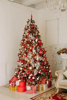 Lindamente decorada árvore de natal com muitos presentes debaixo dela