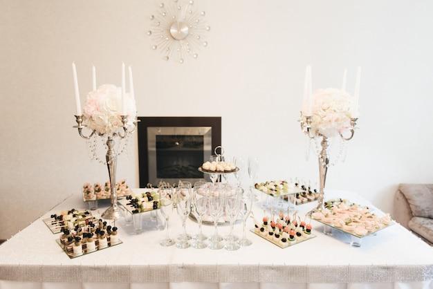 Lindamente decorado, mesa de banquete com hambúrgueres, profiteroles, saladas e lanches frios. variedade de deliciosos petiscos deliciosos em cima da mesa
