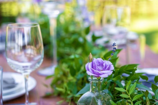 Lindamente decorado mesa de madeira em um café ao ar livre do verão. ramo verde e decoração de mesa de flores frescas.