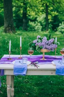 Lindamente servido mesa ao ar livre com flores e decoração