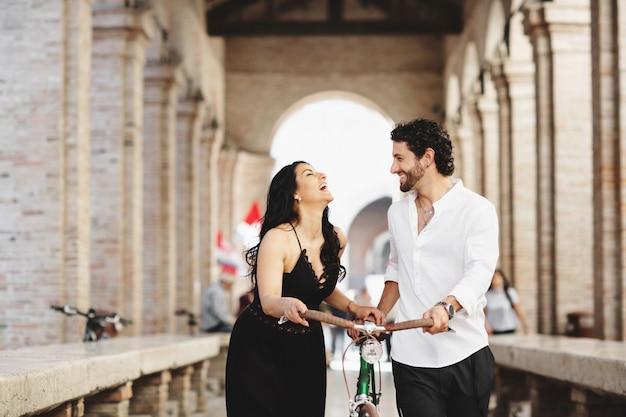 Lindamente vestida, homem e mulher estão andando na cidade velha com uma bicicleta