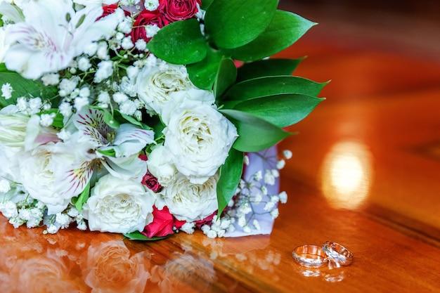 Lindas alianças de casamento encontram-se na superfície de madeira, contra o fundo de um buquê de flores. rd