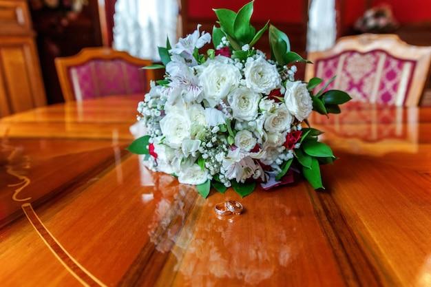 Lindas alianças de casamento encontram-se na superfície de madeira, contra o fundo de um buquê de flores.