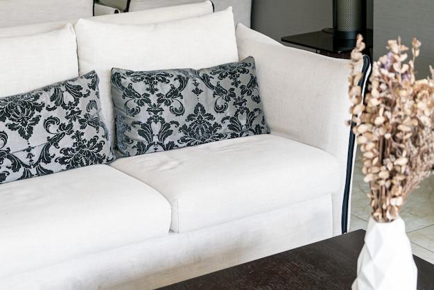 Lindas almofadas no sofá e vaso com flores secas