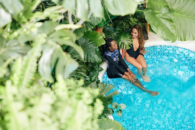 Lindas amigas curtindo uma escapada de fim de semana, refrescando-se em uma piscina com espreguiçadeiras luxuosas ao redor
