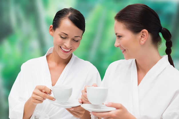 Lindas amigas em roupões tomando chá de ervas