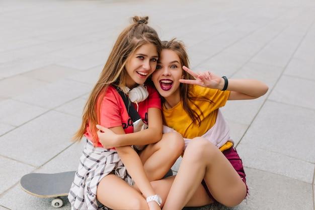 Lindas amigas em trajes coloridos da moda brincando sentadas no chão