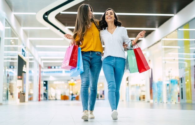 Lindas amigas felizes e animadas com sacos de papel andando pelo shopping